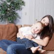 Young mother and toddler son enjoying playtime at home on the couch. — Stock Photo