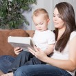 Young mother showing toddler to read on tablet — Stock Photo