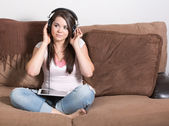 Smiling young woman sitting cross legged on couch listening to music on large headphones on mobile multimedia computer tablet. — Stock Photo