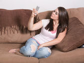 Cute young Caucasian woman taking duckface self portrait on cell phone — Stock Photo