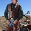 Handsome older retired man in desert leaning against motorcycle staring off into the distance — Stock Photo