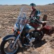 Rugged retired man with his motor cycle in the southwest. — Stock Photo