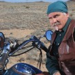 Handsome older man leaning against large motorcycle outdoors in brown desert — Stock Photo #27911083