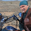 Handsome older man leaning against large motorcycle outdoors in brown desert — Stock Photo