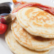 Serving of pancakes and bacon with syrup — Stock Photo