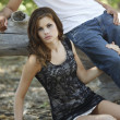 Stock Photo: Pretty brunette womsitting on ground clutching her boyfriend's leg outdoors