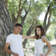 Cute brunette couple outdoors in park on a date wearing white — Stockfoto