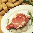 Seven pound standing rib eye beef roast on its side on a white plate dressed with garlic, rosemary and potatoes — Stock Photo