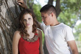 Intense young couple leaning against cottonwood tree in woods — Stock Photo