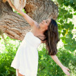 Beautiful Hispanic Woman in nature leaning against large tree trunk — Stock Photo #28292355