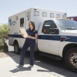 Nurse reviewing patient file standing next to ambulance and red fire ems paramedic truck — Stok fotoğraf