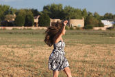 Carefree young woman in black and white print dress running in early morning sunlight outdoors in a meadow — Стоковое фото