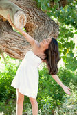 Beautiful Hispanic Woman in nature leaning against large tree trunk — Stock Photo