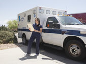 Nurse reviewing patient file standing next to ambulance and red fire ems paramedic truck — Stock Photo