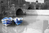 Black and white harbour with two blue boats — Stock Photo
