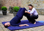 Assisted shoulder stand — Stockfoto
