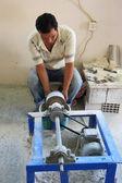 Trabalhador se sentou no chão usando um torno — Fotografia Stock