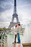 Milující pár líbání poblíž Eiffelova věž v Paříži — Stock fotografie