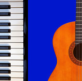 Guitar, piano on blue. — Stock Photo
