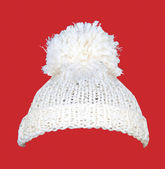 White knitted wool hat on red — Stock Photo
