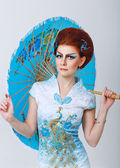Geisha in a smart dress with umbrella — Stock Photo
