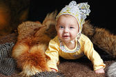 Baby, fox pelt and hauberk — Stock Photo