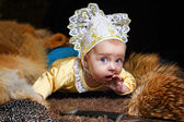 Baby, fox pelt and sword — Stock Photo