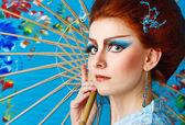 Geisha in a smart dress with umbrella — Stock Photo