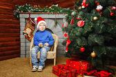 Мальчик сидит возле елки и подарки — Стоковое фото