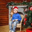 Boy sits near Christmas tree and gifts — Stock Photo