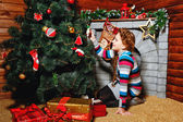 Girl sitting near Christmas tree — Stok fotoğraf