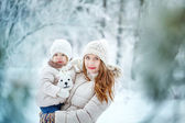 Mother holds daughter on hands in winter forest — Stockfoto