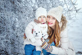 Mother holds daughter on hands in winter forest — Foto de Stock
