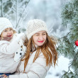 Mother holds daughter on hands in winter forest — Stock Photo