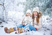 Mother and daughter in winter forest — Stock Photo