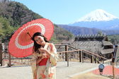 Japanese kimono woman with traditional red umbrella with Fuji in the background — Stock Photo