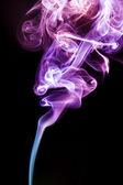 Multicolor smoke rises up on a black background — Stock Photo