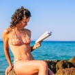 Beautiful girl in bikini is reading a book at the beach on sunset — Stok fotoğraf