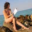 Beautiful girl in bikini is reading a book at the beach on sunset — Stock Photo