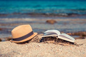 Book and a hat at the beach — Stock Photo