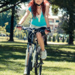 Beautiful redhead girl riding and cycling a bike in a city park — Stock Photo