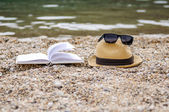 Book at beach during summer reading — Stock Photo
