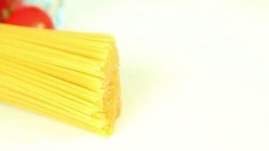 Italian food ingredients on white background, tomato with pasta spaghetti — Stock video