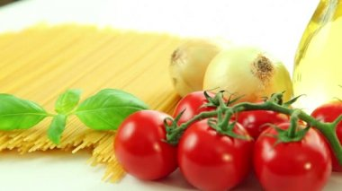 Italian food ingredients on white background, tomato with macaroni spaghetti, garlic, pepper, onion, olive oil and basil — Stock Video