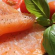 Foto Stock: Rose coloured smoked salmon on toast, basil and tomatoes