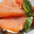 Rose coloured smoked salmon on toast, basil and tomatoes — Stock Photo #29738819