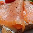 Rose coloured smoked salmon on toast, basil and tomatoes — Stock Photo