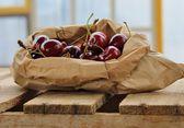 Sacchetto di carta marrone di ciliegie mature — Foto Stock