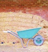 Brick wall with hay bales and wheel barrow — Stock Photo