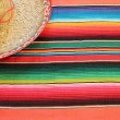 Fiesta mexican poncho rug in bright colors with sombrero background with copy space — Stock Photo #39987567